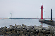 harbor entrance with red and white lighthouse