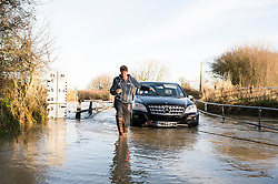 © Licensed to London News Pictures. 20/12/2013. Billericay, UK. After a night of heavy rain again, water levels rose to trap another vehicle attempting to negotiate the notorious Buttsbury Wash. The Mercedes 4X4 was driven by the lady taking her husband to the station. The vehicle almost made it through before stalling. She was forced to climb out of ther window and was able to attach a tow rope to a van that came to assist. The worst problem was cold wet feet for the driver. Photo credit : Simon Ford/LNP
