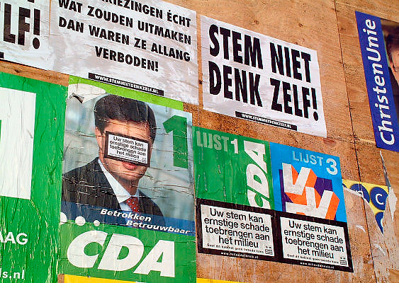 Nederland, Nijmegen, 12-1-2003..Verkiezingsaffiches op verkiezingsbord overgeplakt met anti verkiezings kreten. Vertrouwen politiek, democratie, tweede kamer verkiezingen, stemmen, milieudefensie, cda, vvd..Foto: Flip Franssen/Hollandse Hoogte