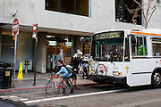 Fietsers zetten hun fiets voorop de stadsbus in de Financial District in San Francisco waar veel hoofdkantoren van banken en grote ondernemingen zijn gevestigd. De Amerikaanse stad San Francisco aan de westkust is een van de grootste steden in Amerika en kenmerkt zich door de steile heuvels in de stad.<br /> <br /> Cyclists put their bikes on a bus at the Financial District of San Francisco where headquarters of banks and financial companies are located. The US city of San Francisco on the west coast is one of the largest cities in America and is characterized by the steep hills in the city.