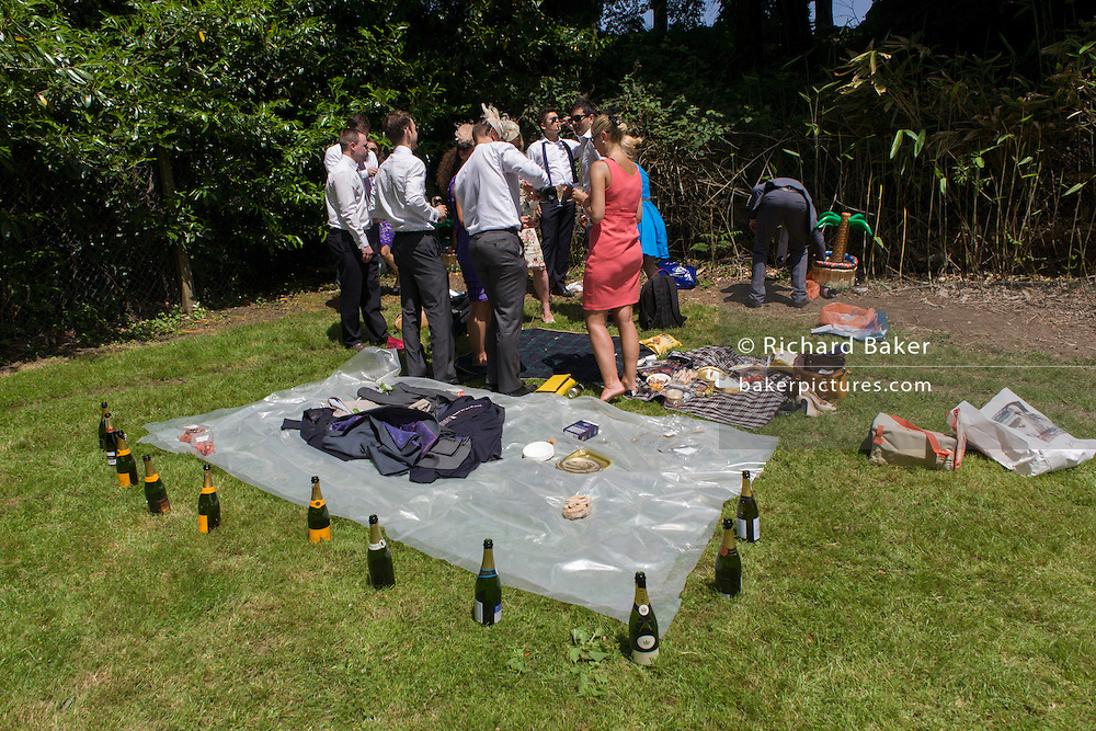 Wealthy punters with bottles of empty Champagne laid out enjoy a morning car park party on grass, hours before the annual Royal Ascot horseracing festival in Berkshire, England. Royal Ascot is one of Europe's most famous race meetings, and dates back to 1711. Queen Elizabeth and various members of the British Royal Family attend. Held every June, it's one of the main dates on the English sporting calendar and summer social season. Over 300,000 people make the annual visit to Berkshire during Royal Ascot week, making this Europe's best-attended race meeting with over £3m prize money to be won.