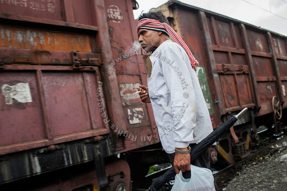 An Indian man is smocking a cigarette while waiting for a commercial train to pass through New Arif Nagar, one of the water-affected colonies surrounding the abandoned Union Carbide (now DOW Chemical) industrial complex in Bhopal, Madhya Pradesh, India.
