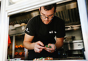 Executive chef John McConnell puts the finishing touches on dishes at the Clif Family Bruschetteria, a bruschetta truck parked outside the Velo Vino tasting room in St. Helena, Calif., on Sunday, October 11, 2015.