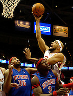 PHOTO BY DAVID RICHARD.Drew Gooden puts up a shot over Rasheed Wallace, left, and Ben Wallace of Detroit last night in the first half.