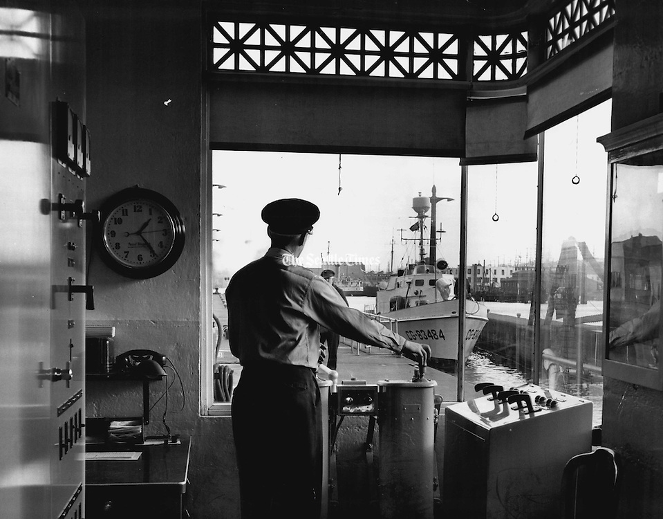 A lockman, working in wide-windowed house of levers at the Government Locks, opened a gate to permit a Coast Guard patrol boat to pass from Salmon Bay and its fresh water to the salt water of Shilshole Bay. From this control room the lockmen opened and closed the gates of the small lock. (Josef Scaylea / The Seattle Times, 1950)