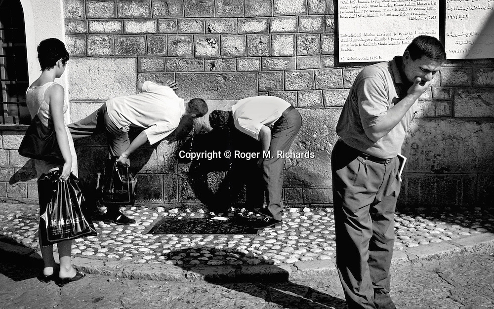 Pedestrians stop to have a drink of ice-cold water from the mountains from a fountain outside the old Gazi Husref Begova mosque in Sarajevo's old town district of Bascarsija, August, 1999. PHOTO BY ROGER RICHARDS/DV REPORTER