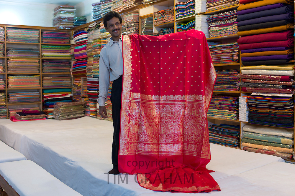 Indian man displays sari fabric at silk factory at Bressler near Varanasi, Benares, Northern India