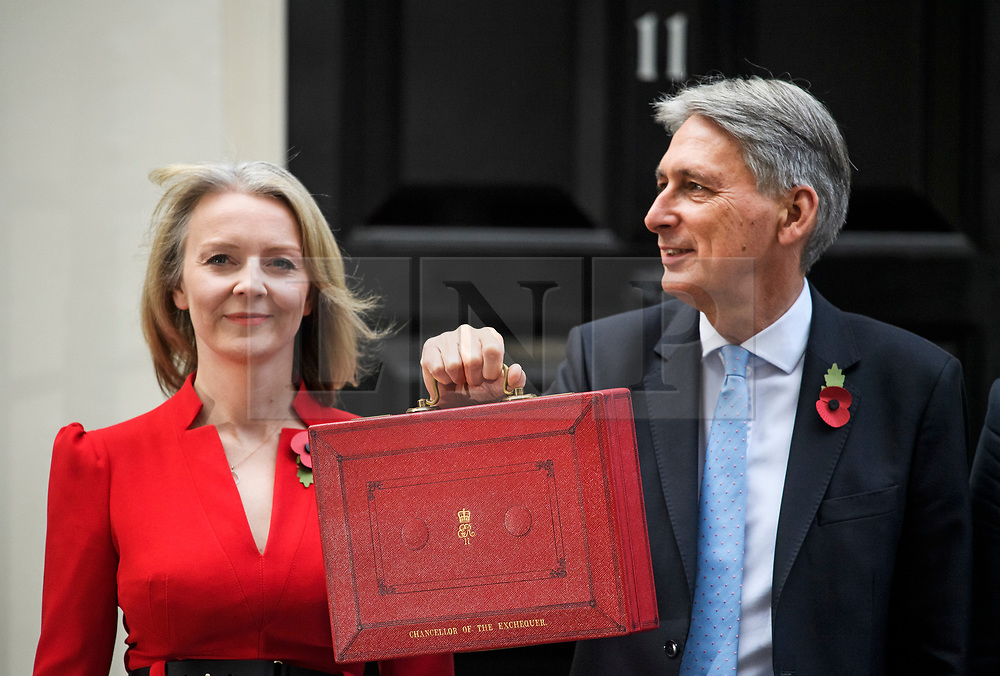 © Licensed to London News Pictures. 29/10/2018. London, UK. Chief Secretary to the Treasury LIZ TRUSS stands next to Chancellor PHILIP HAMMOND as he holds his red dispatch box on the steps of Number 11 Downing Street in London, before presenting his Budget to Parliament. This will be the last budget before the UK is due to exit the European Union in March of 2019. Photo credit: Ben Cawthra/LNP