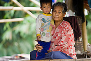 18 FEBRUARY 2008 -- BONG TI, KANCHANABURI, THAILAND: A Karen woman and her grandson in a refugee village near the Bamboo School in Bong Ti, Thailand, about 40 miles from the provincial capital of Kanchanaburi. Sixty three children, most members of the Karen hilltribe, a persecuted ethnic minority in Burma, live at the school under the care of Catherine Riley-Bryan, whom the locals call MomoCat (Momo is the Karen hilltribe word for mother). She provides housing, food and medical care for the kids and helps them get enrolled in nearby Thai public schools. Her compound is about a half mile from the Thai-Burma border. She also helps nearby Karen refugee villages by digging water wells for them and providing medical care. Thai authorities have allowed the refugees to set up the village very close to the border but the villagers are not allowed to own land in Thailand and they can't legally leave the area to get jobs in Thailand.   Photo by Jack Kurtz