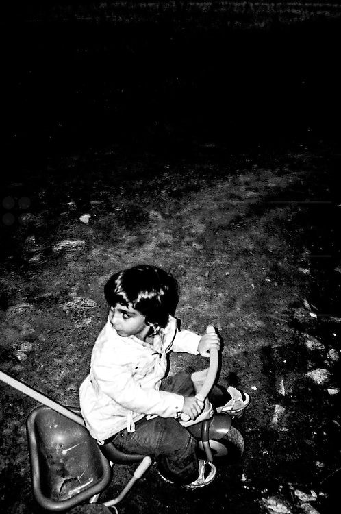 A kid on his stroller is looking at his father during a walk on the surroundings of the center at night. FEDASIL Sugny asylum center. Sugny, Belgium. July 2015. I took these photographs during an international volunteer program that I liderate with an international volunteering group.