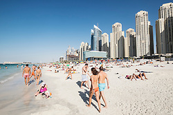 Busy public beach at Jumeirah Beach Resort (JBR) at Marina District in Dubai United Arab Emirates