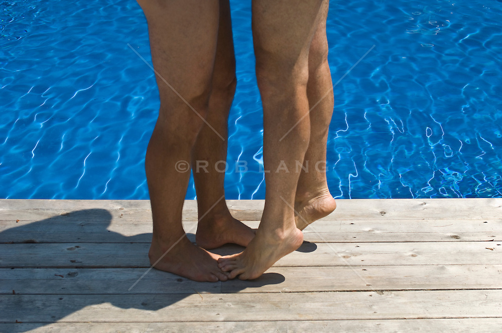 man standing on another man's toes by a swimming pool