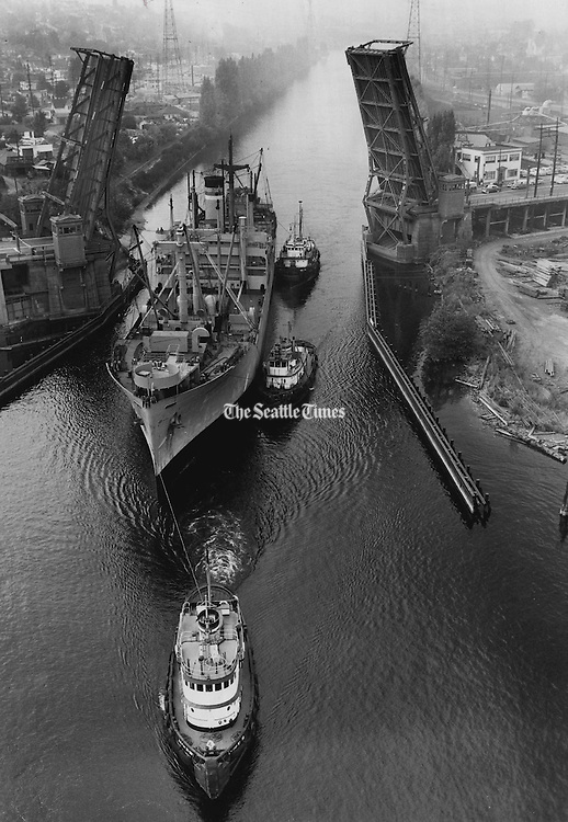 Her Work is Done: The transport Lieut. Raymond Beaudoin, which has completed her emergency duty of carrying troops for the Korean war, was towed under the Fremont Bridge on her way to the Lake Union Drydock Co. yard. She will be prepared there for joining the reserve fleet at Olympia. (Josef Scaylea / The Seattle Times, 1952)