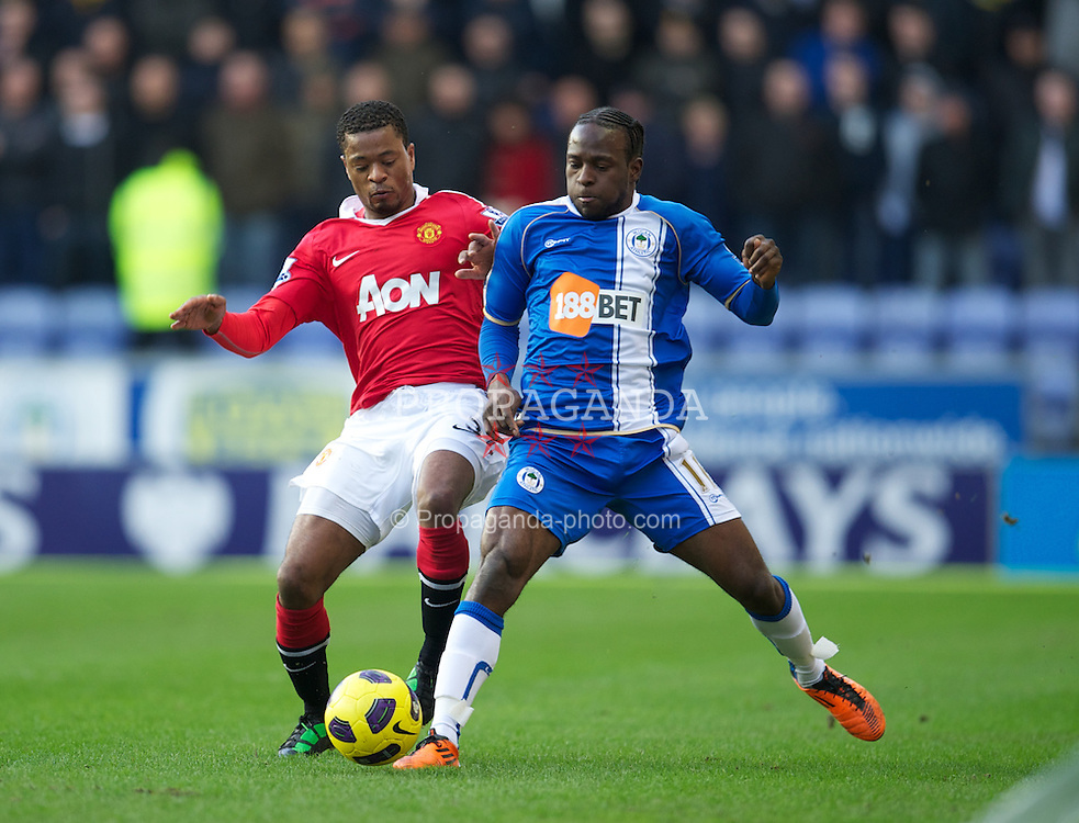 WIGAN, ENGLAND - Saturday, February 26, 2011: Manchester United's Patrice Evra and Wigan Athletic's Victor Moses during the Premiership match at the DW Stadium. (Photo by David Rawcliffe/Propaganda)
