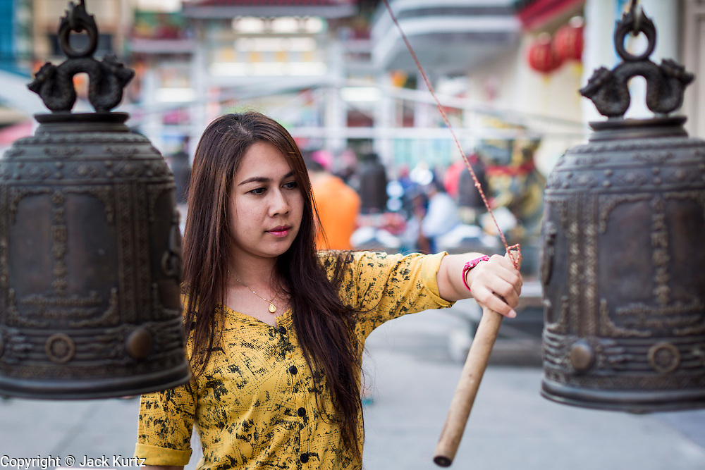 09 FEBRUARY 2014 - HAT YAI, SONGKHLA, THAILAND: A woman rings a prayer bell during Lunar New Year in the Tong Sia Siang Tueng temple in Hat Yai. Hat Yai was originally settled by Chinese immigrants and still has a large ethnic Chinese population. Chinese holidays, especially Lunar New Year (Tet) and the Vegetarian Festival are important citywide holidays.     PHOTO BY JACK KURTZ