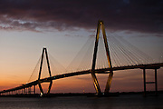 Sunset over the Arthur Ravenel Jr. Bridge, also known as the New Cooper River Bridge in Charleston, SC. The bridge is a cable-stayed bridge over the Cooper River in South Carolina, connecting downtown Charleston to Mount Pleasant. The eight lane bridge opened in 2005 to replace two obsolete cantilever truss bridges. The bridge has a main span of 1,546 feet (471 m), the second longest among cable-stayed bridges in the Western Hemisphere. It was built using the design-build method and was designed by Parsons Brinckerhoff.