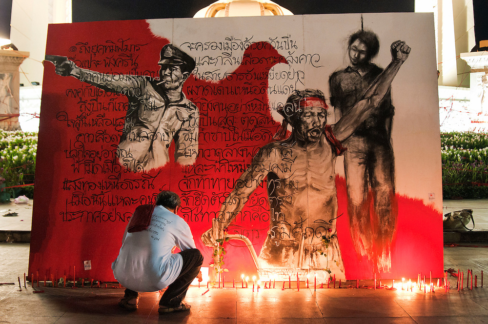 A Red Shirt supporter lights candles under an artists rendering at Democracy Monument, Bangkok, Thailand.