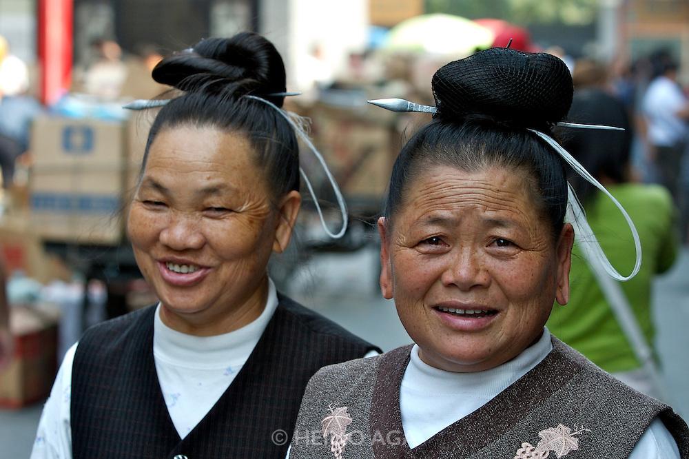Panjiayuan weekend market. Two Southern tribeswomen from an ethnic minority.