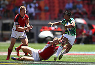 Justin Geduld of South Africa attempts to break the tackle during the HSBC Sevens World Series Port Elizabeth Leg held at the Nelson Mandela Bay Stadium on 7th December 2013 in Port Elizabeth, South Africa. Photo by Shaun Roy/Sportzpics