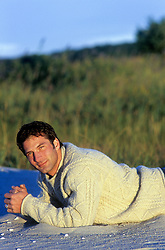 man in a big sweater relaxing at the beach in The Fall