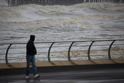 "© Licensed to London News Pictures . 10/12/2014 . Blackpool , UK . A man looks out at choppy seas from Blackpool Promenade . An explosive cyclogenesis - a fast developing storm in which air pressure falls rapidly - known as a "" weather bomb "" - hits the North of England , bringing storms to the region . Photo credit : Joel Goodman/LNP"