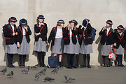 As weather warms up after a long winter, English schoolgirls visit London's Trafalgar Square.