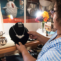 Roxanne Seoutewa, a Zuni Pueblo Petti-point silversmith holds up one of her pieces in her home studio Thursday, July 4 in Zuni.