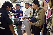"02 OCTOBER 2009 -- BANGKOK, THAILAND: Volunteers from the Poh Teck Tung foundation tend to a woman who committed suicide in her home in Bangkok. Neighbors said the woman drank mosquito poison after an argument with her husband. The 1,000 plus volunteers of the Poh Teck Tung Foundation are really Bangkok's first responders. Famous because they pick up the dead bodies after murders, traffic accidents, suicides and other unplanned, often violent deaths, they really do much more. Their medics respond to medical emergencies, from minor bumps and scrapes to major trauma. Their technicians respond to building collapses and traffic accidents with heavy equipment and the ""Jaws of Life"" and their divers respond to accidents in the rivers and khlongs of Bangkok. The organization was founded by Chinese immigrants in Bangkok in 1909. Their efforts include a hospital, college tuition for the poor and tsunami relief.   PHOTO BY JACK KURTZ"