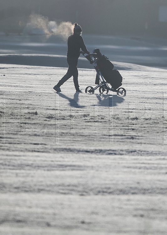© Licensed to London News Pictures. 16/12/2017. London, UK. A golfer walks through a frost covered golf course in Richmond Park. Parts of the UK are experiencing freezing temperatures today with snow expected in parts. London, UK. Photo credit: Ben Cawthra/LNP