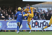 Bayo Akinfenwa of AFC Wimbledon tussles with Ryan Tafazolli of Mansfield Town during the Sky Bet League 2 match between AFC Wimbledon and Mansfield Town at the Cherry Red Records Stadium, Kingston, England on 16 January 2016. Photo by Stuart Butcher.