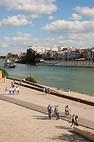 local people walking along the river in sevilla, spain