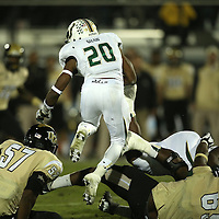 South Florida Bulls running back Marcus Shaw (20) leaps over defenders during an NCAA football game between the South Florida Bulls and the 17th ranked University of Central Florida Knights at Bright House Networks Stadium on Friday, November 29, 2013 in Orlando, Florida. (AP Photo/Alex Menendez)