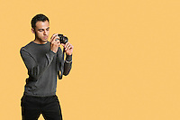 confident young man with digital camera over colored background
