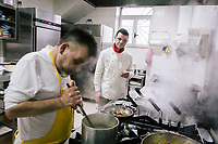 NAPLES, ITALY - 20 MARCH 2018: Raffaele Esposito (center) waits for his brother Carmine (left) to finish a savoy cabbage risotto at the Pizzeria e Trattoria Vigliena in Naples, Italy, on March 20th 2018.<br /> <br /> Pizzeria e Trattoria Vigliena is a restaurant outside of the city center and adjacent to the port. At lunch, the place is packed with workers from the docks and ship owners and workers from the recently built Marina Vigliena.<br /> <br /> The restaurant is owned by Raffaele Esposito, Concetta's son and the third generation of a family of chefs who founded this restaurant in the middle of the 20th century