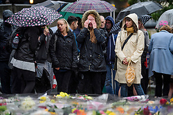 © Licensed to London News Pictures. 06/06/2017. London, UK.  An emotional woman watches over floral tributes during a minutes silence at London Bridge in central London for those who lost their life in a terrorist attack on Saturday evening. Three men attacked members of the public  after a white van rammed pedestrians on London Bridge.   Ten people including the three suspected attackers were killed and 48 injured in the attack. Photo credit: Ben Cawthra/LNP