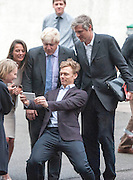 © Licensed to London News Pictures. 08/10/2014. Richmond, UK. A man takes a selfie with Boris Johnson and Zac Goldsmith.  The Mayor of London, Boris Johnson, and Zac Goldsmith MP tour 'The Poppy Factory' in Richmond, Surrey, today 9th October 2014.  Melanie Waters, the Chief Executive, briefed the Mayor and Zac Goldsmith on The Poppy Factory's 'Getting You Back to Work' initiative. To date, The Poppy Factory has supported nearly 500 wounded, injured or sick ex-service men and women back into the workplace through this new, nationwide initiative, through connections with commercial organisations like Transport for London. The goal is to help over 1,000 veterans by 2018. Employees at The Poppy Factory have made some 13 million poppies, 950,000 thousand remembrance crosses and 96,000 wreaths for The Royal British Legion Remembrance events in November. The Annual Field of Remembrance at Westminster Abbey is also planned and delivered by The Poppy Factory. Photo credit : Stephen Simpson/LNP