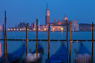 The church and campanile on the island of San Giorgio Maggiore as seen from San Marco area of Venice with a row of gondolas in front. The church of San Giorgio Maggiore was designed by Andrea Palladio and work began in 1566. It is one of Palladio's greatest architectural achievements.