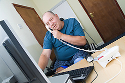 Disabled man at work in an office using a computer and talking on the telephone,