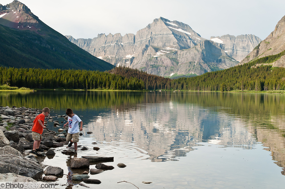 """Children plan in water at Swiftcurrent Lake, in Glacier National Park, Montana, USA. Since 1932, Canada and USA have shared Waterton-Glacier International Peace Park, which UNESCO declared a World Heritage Site (1995) containing two Biosphere Reserves (1976). Rocks in the park are primarily sedimentary layers deposited in shallow seas over 1.6 billion to 800 million years ago. During the tectonic formation of the Rocky Mountains 170 million years ago, the Lewis Overthrust displaced these old rocks over newer Cretaceous age rocks. Glaciers carved spectacular U-shaped valleys and pyramidal peaks as recently as the Last Glacial Maximum (the last """"Ice Age"""" 25,000 to 13,000 years ago). Of the 150 glaciers existing in the mid 1800s, only 25 active glaciers remain in the park as of 2010, and all may disappear by 2020, say climate scientists."""