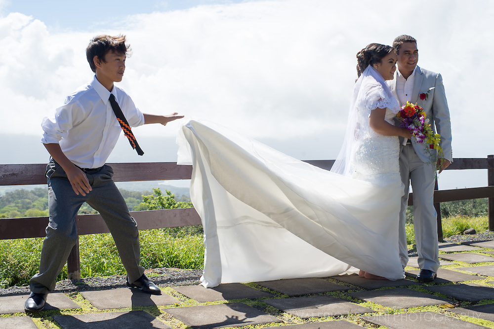 A boy raises the wedding dress of the bride before running away in the aim to create a wind effect to the official portraits being taken by their photographer.