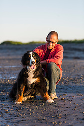 A man walks his dog at Seapoint Beach in Kittery, Maine.