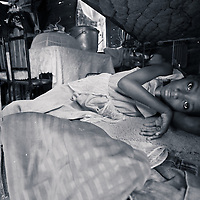 A girl stares out from her bed in a corrugated iron house in a camp in Port au Prince, Haiti