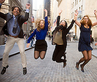 Celebrating a victory, business team members jump for joy downtown