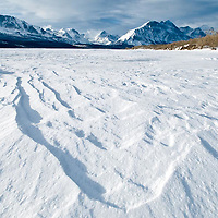 frozen snow coverd saint mary's lake, low angle wide moutain backdrop from snow coverd lake, glacier national park