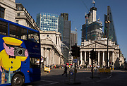 With the Bank of England on the left and neo-classical columns of Cornhill Exchange beneath new skyscrapers rising above the City of London - the capital's financial district (aka The Square Mile), a London sightseeing bus passes through Bank Triangle with on 19th April 2018, in London, England.
