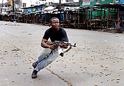 A Liberian government gunman fires accross the 'Old bridge' to keep LURD (Liberians United for Reconciliation and Democracy) rebels from crossing to the Capital Monrovia in a fierce gunfight lasting several hours 24 July 2003. This is day six of continued fighting in the capital which has seen thousands displaced and more than 600 dead.The fighting is centered around 2 strategic bridges, the New and Old bridge, which provide access to the city.<br /> EPA PHOTO/NIC BOTHMA