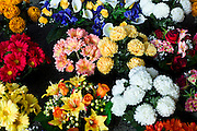 Fabric artificial flowers gerbera, chrysanthemum, lilies on sale at market in La Reole, Bordeaux region of France