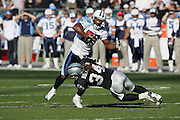 OAKLAND, CA - DECEMBER 19:  Wide receiver Derrick Mason #85 (caught 9 passes for 121 yards and a touchdown) of the Tennessee Titans gets tackled by safety Ray Buchanan #34 of the Oakland Raiders at Network Associates Coliseum on December 19, 2004 in Oakland, California. The Raiders defeated the Titans 40-35. ©Paul Anthony Spinelli *** Local Caption *** Derrick Mason;Ray Buchanan
