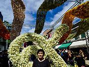22 OCTOBER 2017 - BANGKOK, THAILAND: A woman is photographed in front of Pak Khlong Talat, the flower market, in Bangkok. There is a replica crematorium south of the flower market and the street in front features elaborate displays in the late king's honor. The King died in October 2016 and will be cremated on 26 October 2017.     PHOTO BY JACK KURTZ
