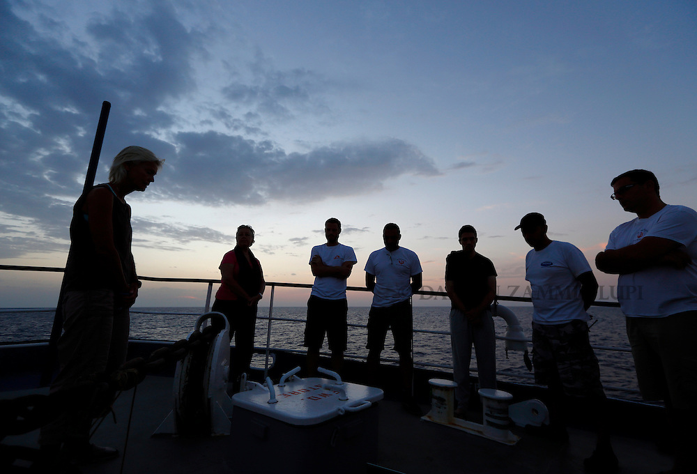Crew members on the Migrant Offshore Aid Station (MOAS) ship MV Phoenix pause for a moment of reflection at dusk during a search for missing migrants after their boat capsized off the coast of Libya August 5, 2015.  A boat packed with up to 700 African migrants capsized in the Mediterranean Sea off the coast of Libya on Wednesday and many were feared dead, officials and aid agencies said. <br /> REUTERS/Darrin Zammit Lupi <br /> MALTA OUT. NO COMMERCIAL OR EDITORIAL SALES IN MALTA
